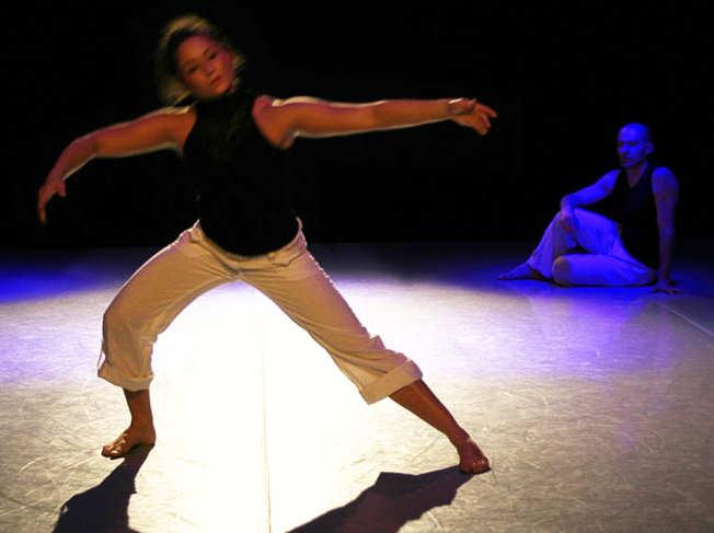 Eine dunkelhaarige Tänzerin bewegt sich mit weit ausgestreckten Armen, im Hintergrund sitzt ein Tänzer auf dem Boden und beobachtet sie.