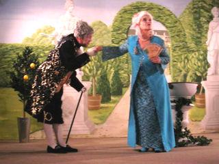 Szene aus einem Theaterstück der nicolaibühne: Ein Mann und eine Frau in Barockkleidern, er verbeugt sich vor ihr und küsst ihr die Hand.