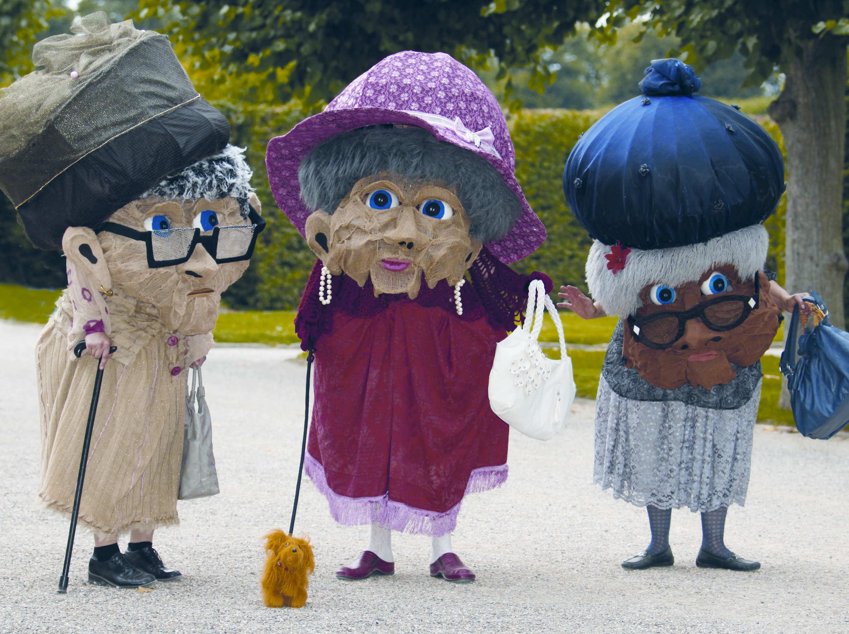 Drei mit riesigen Masken als alte Damen verkleidete Darsteller.