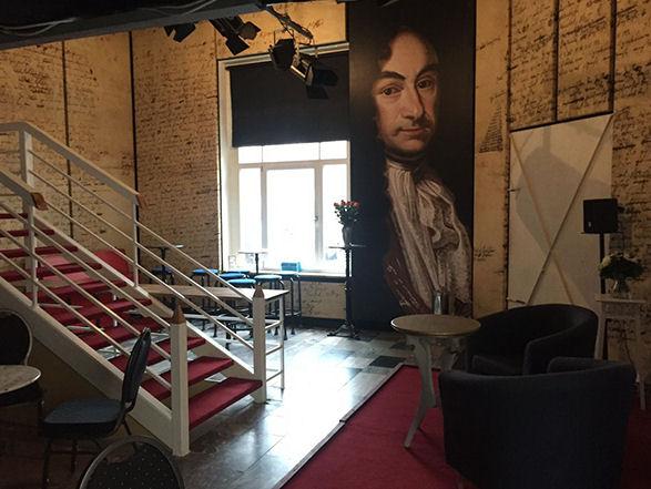 Ein Raum mit Fenster, rotem Teppich, Tischen und Stühlen, einem wandhohen Bild von Leibniz und einer weißen Treppe nach oben,