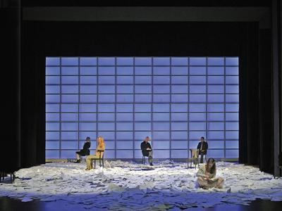 Schauspieler sitzen auf einer Bühne voll von Papierbögen.