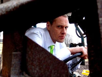 Eine böse schauender Mann sitzt auf einem landwirtschaftlichen Fahrzeug.