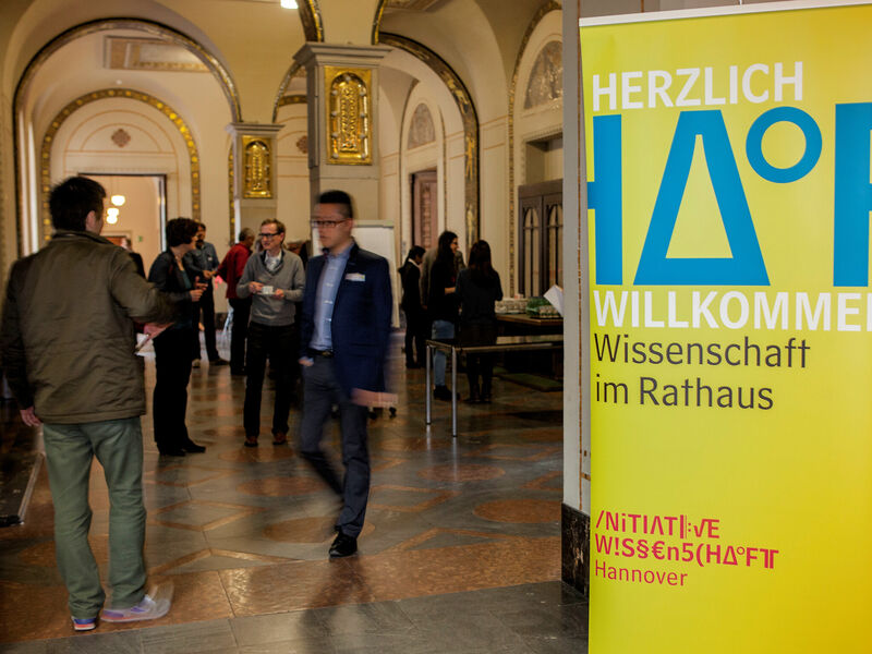 People in a hall with a stand-up display advertising the Hannover Science Initiative.