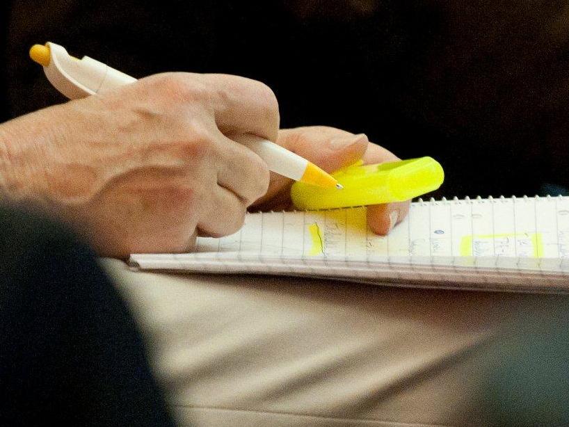 Jemand sitzt auf einem Stuhl, hält einen Schreibblock auf den Beinen und einen Stift in der Hand