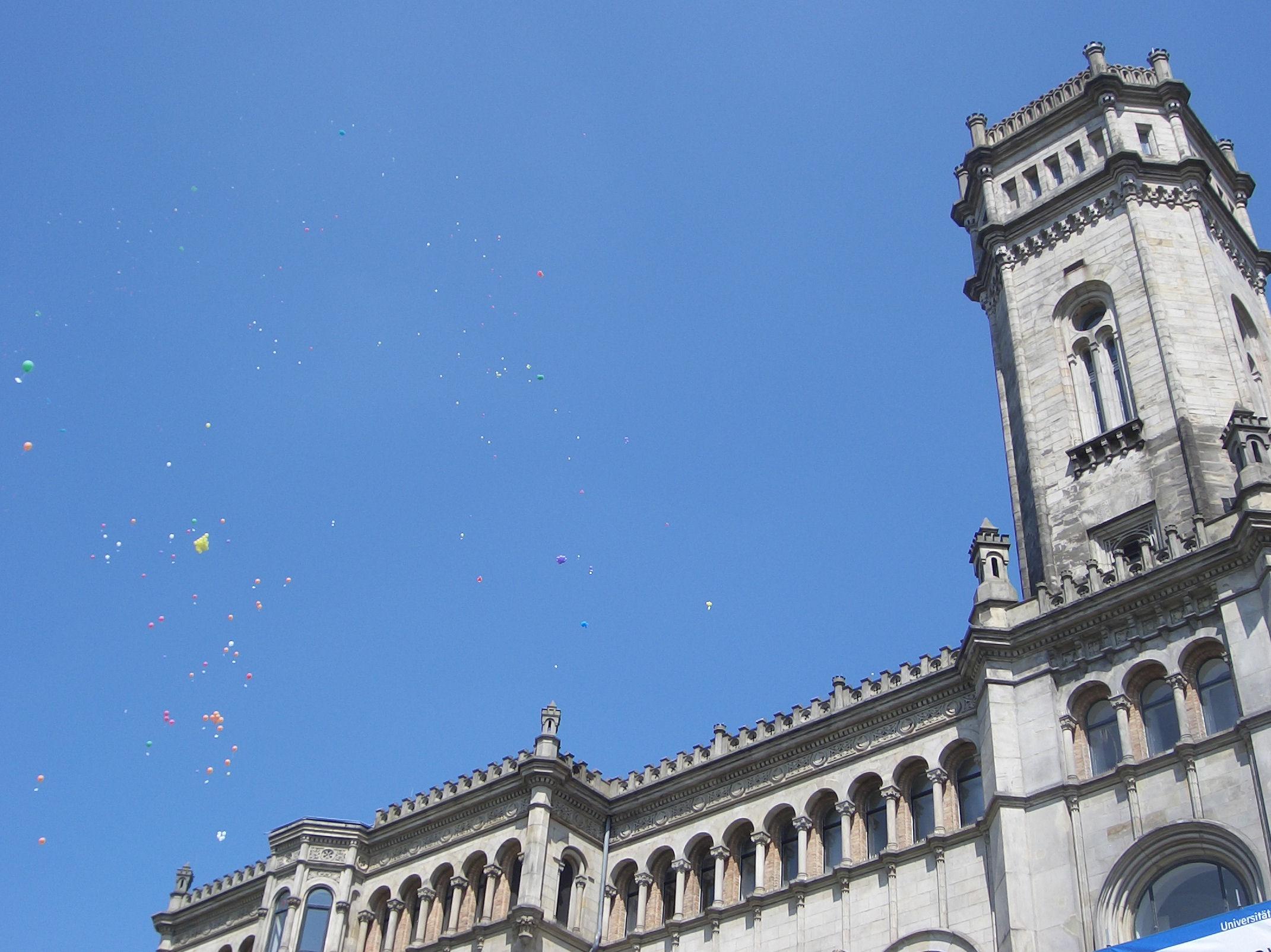 Bunte Ballons vor einem älteren Gebäude.