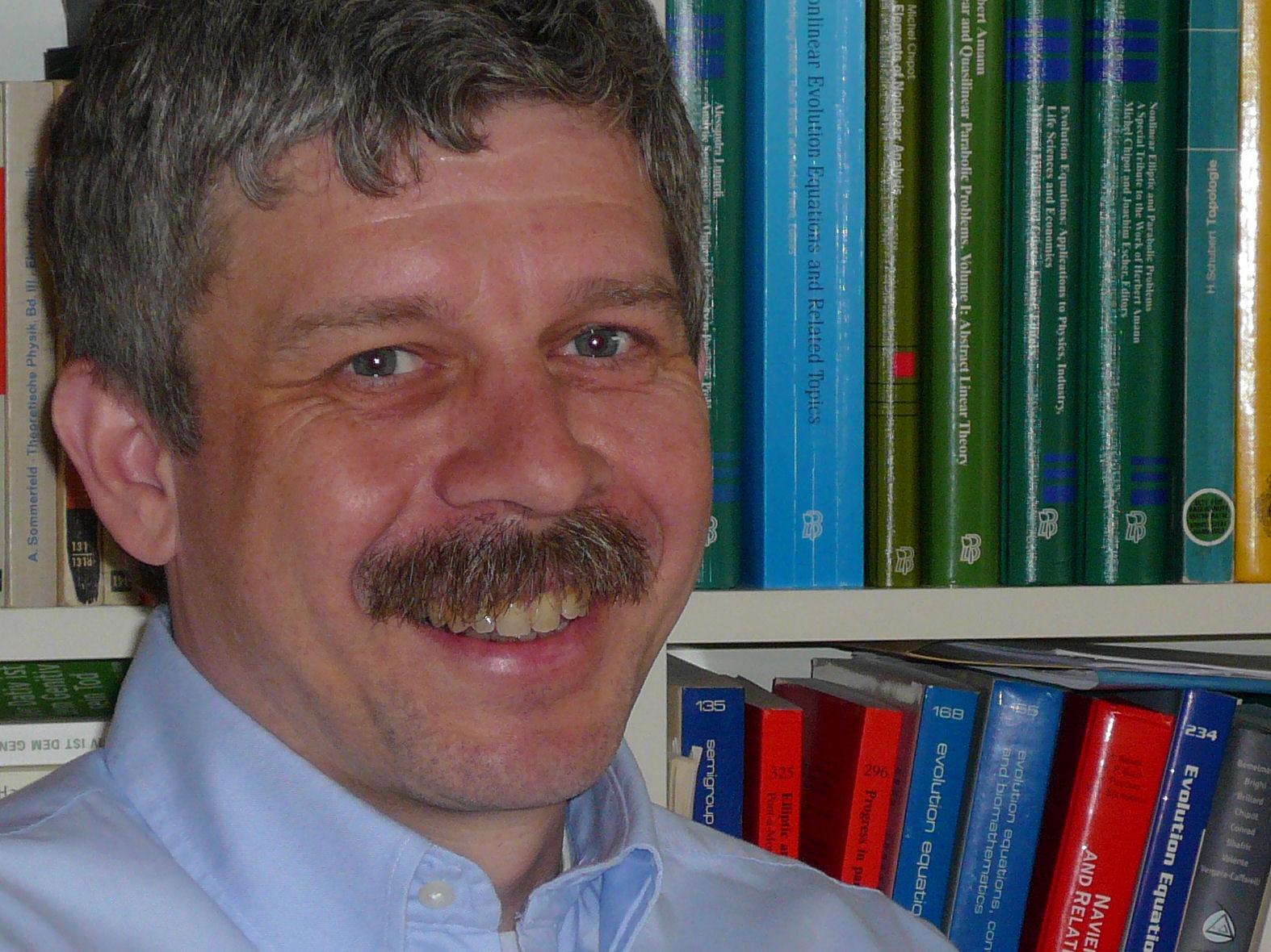 Porträtfoto eines Mannes, im Hintergrund sind Bücher zu sehen.