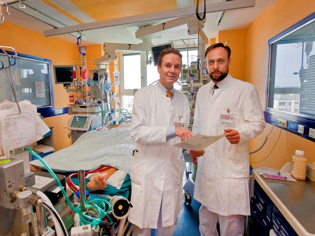 Zwei Männer in weißen Kitteln in einem Raum mit medizinischen Apparaten.
