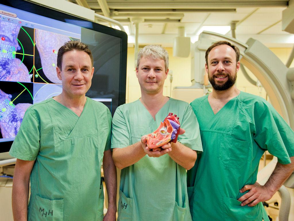 Drei Männer in grünern Kitteln, einer hält ein Modell einer Organs.