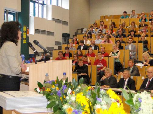 Viele Menschen sitzen in einem Hörsaal, eine Rednerin steht an einem Pult.