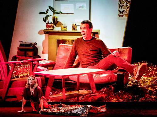 A living room lit in red with a large man on a sofa and a tiny woman on the floor.
