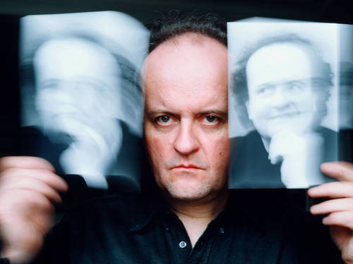 Man holds up two photographs