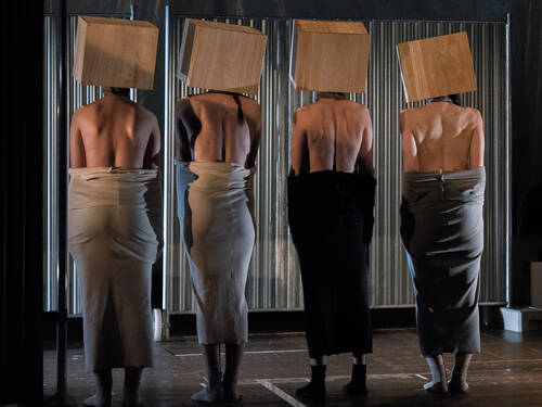 Four women stand on a stage with their backs to the audience and carry boxes over their heads.