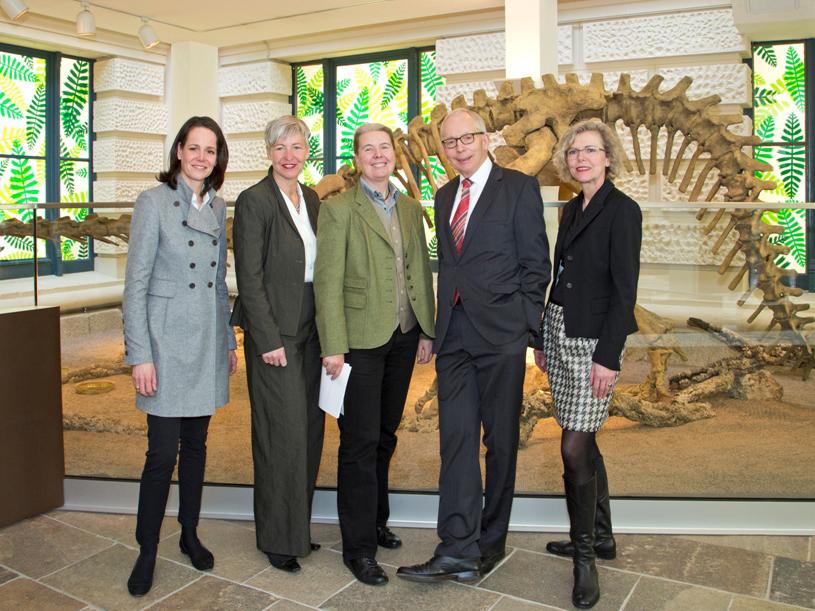 Vier Frauen und ein Mann vor einem Dinosaurierskelett.