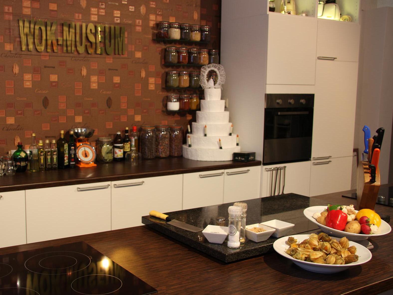 In einer großen Küche hängt ein Schild mit den Worten WOK-Museum an der Wand.