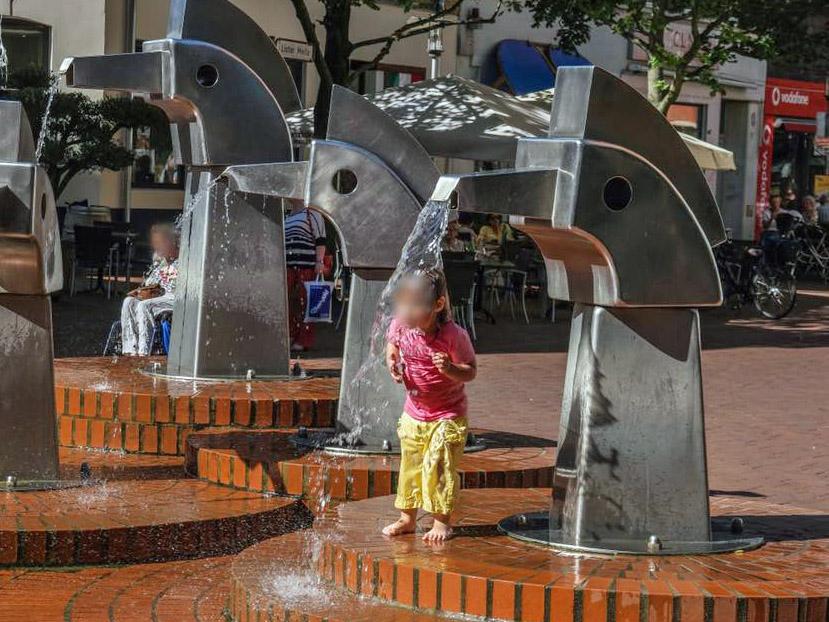 Kleines Kind duscht im Brunnen