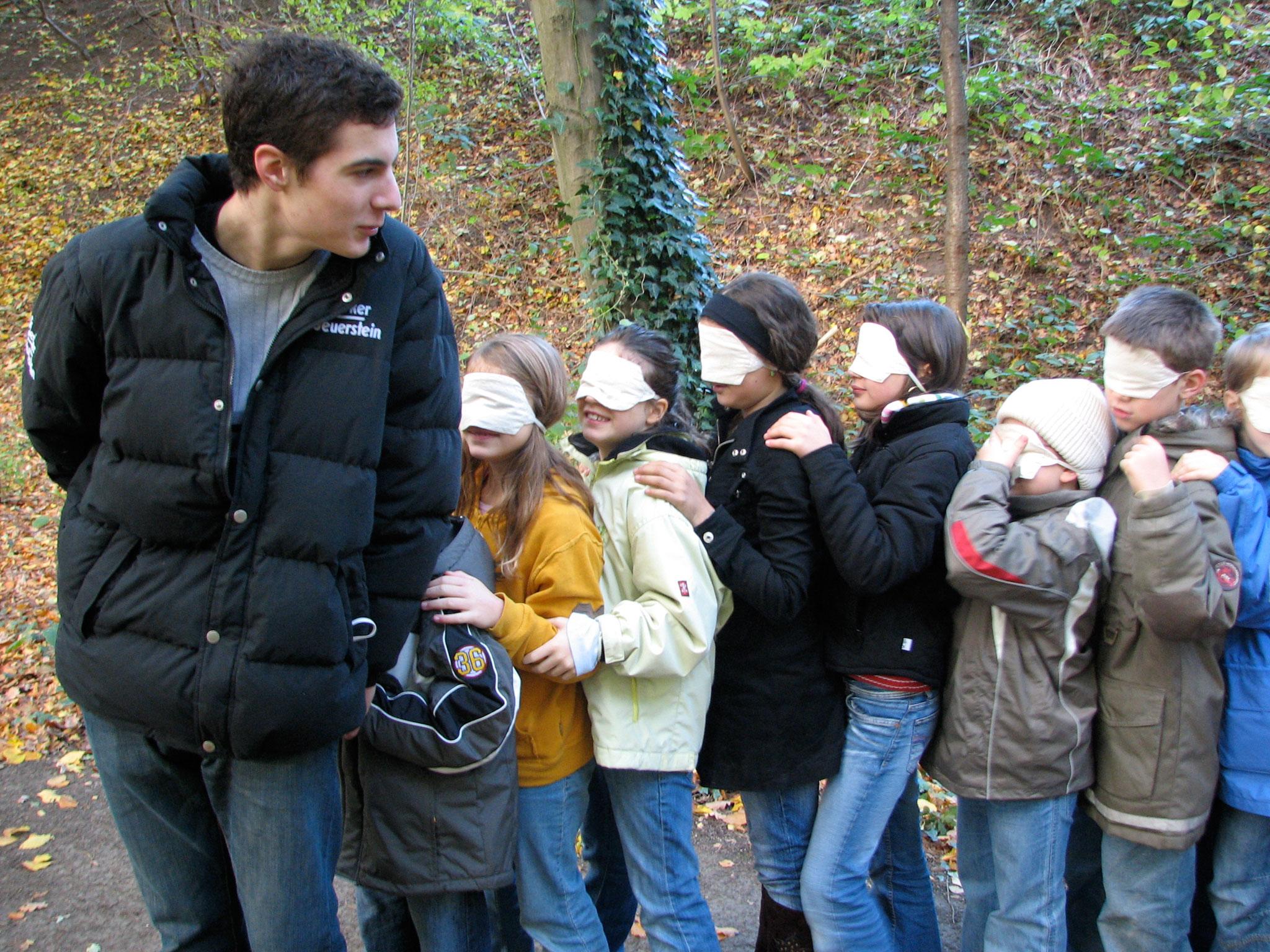 Betreuer führt Kinder mit verbundenden Augen durch den Wald
