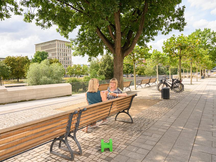 Zwei Personen auf einer Bank an einer Promenade.