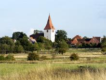 Landschaft mit Dorf und Kirchturm im Hintergrund.