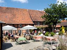 Restaurantbetrieb vor einem Fachwerkhaus. Unter Sonnenschirmen sitzen Menschen die essen und trinken.