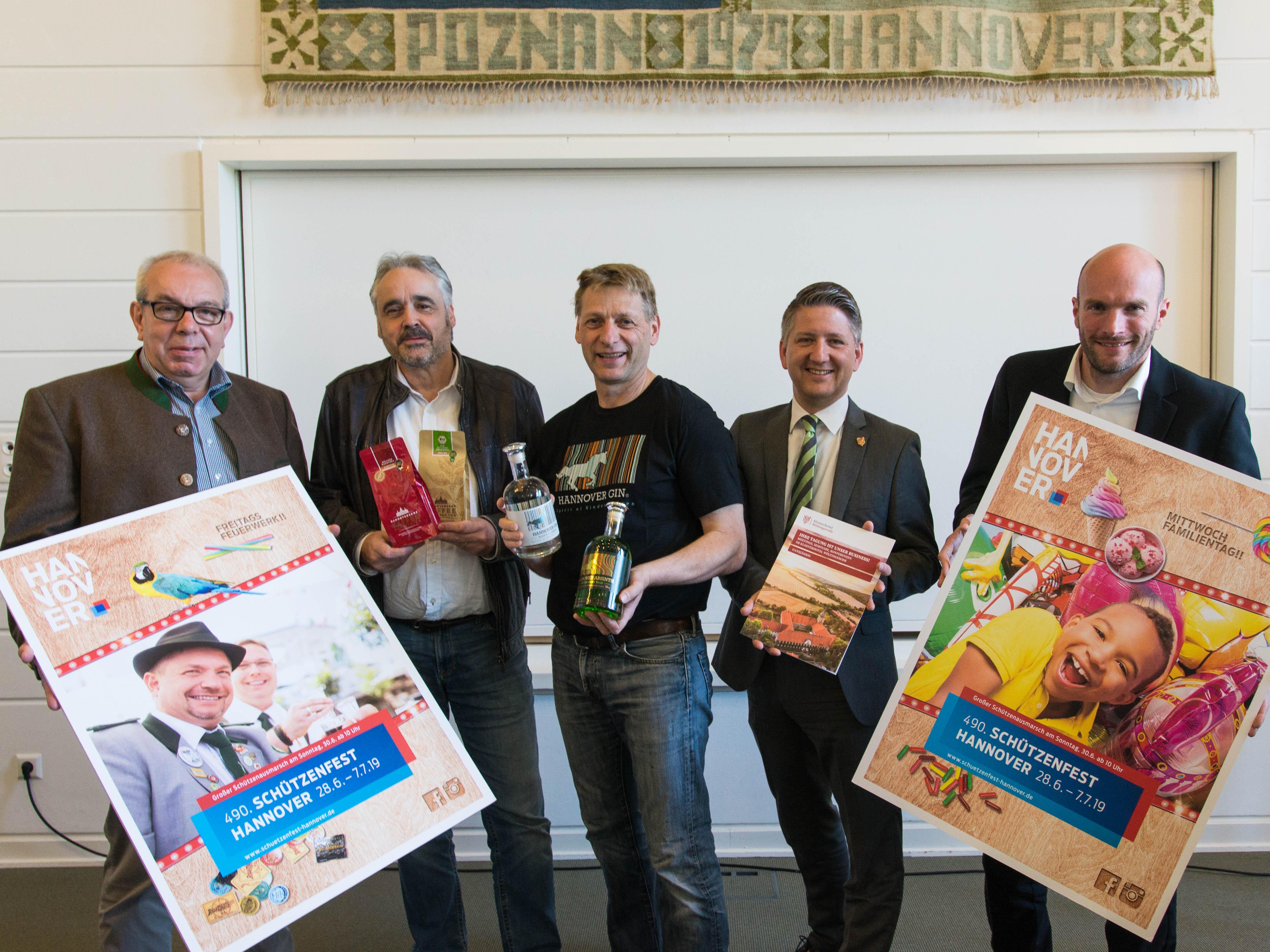 Fünf Männer mit Plakaten, Flaschen, Kaffee und einer Mappe.