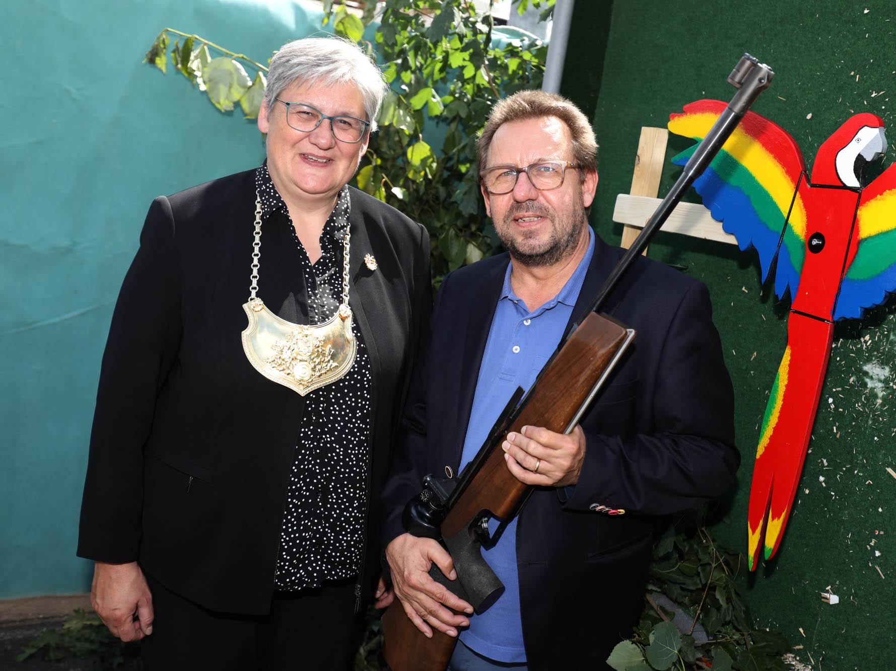 Eine Frau und ein Mann mit einem Gewehr.