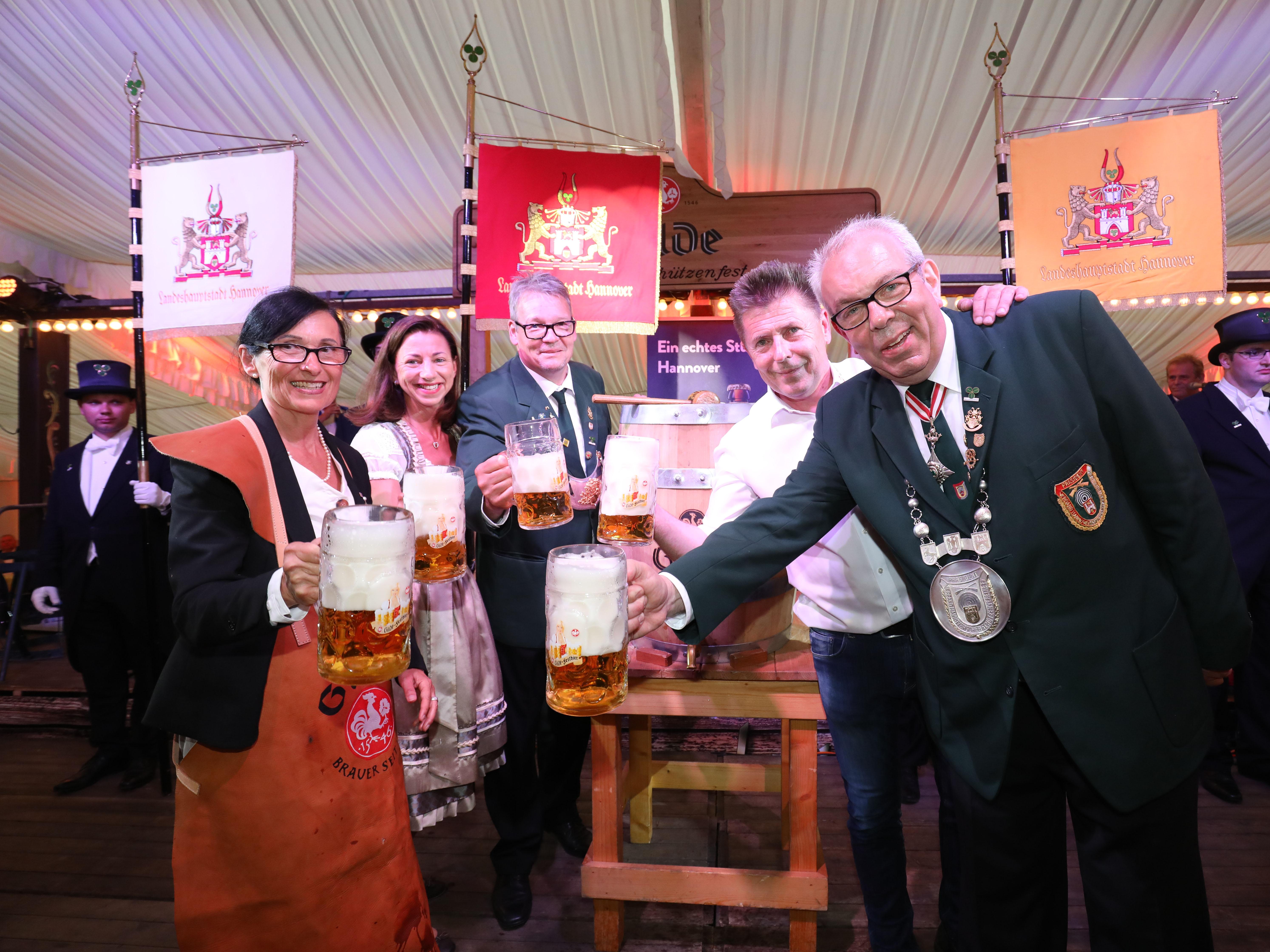 Zwei Frauen und drei Männer um ein Bierfass.