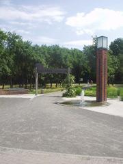 """Weg mit gemauerter Lichtstele und einem Holzbogen mit Aufschrift """"Stadtpark Garbsen"""""""